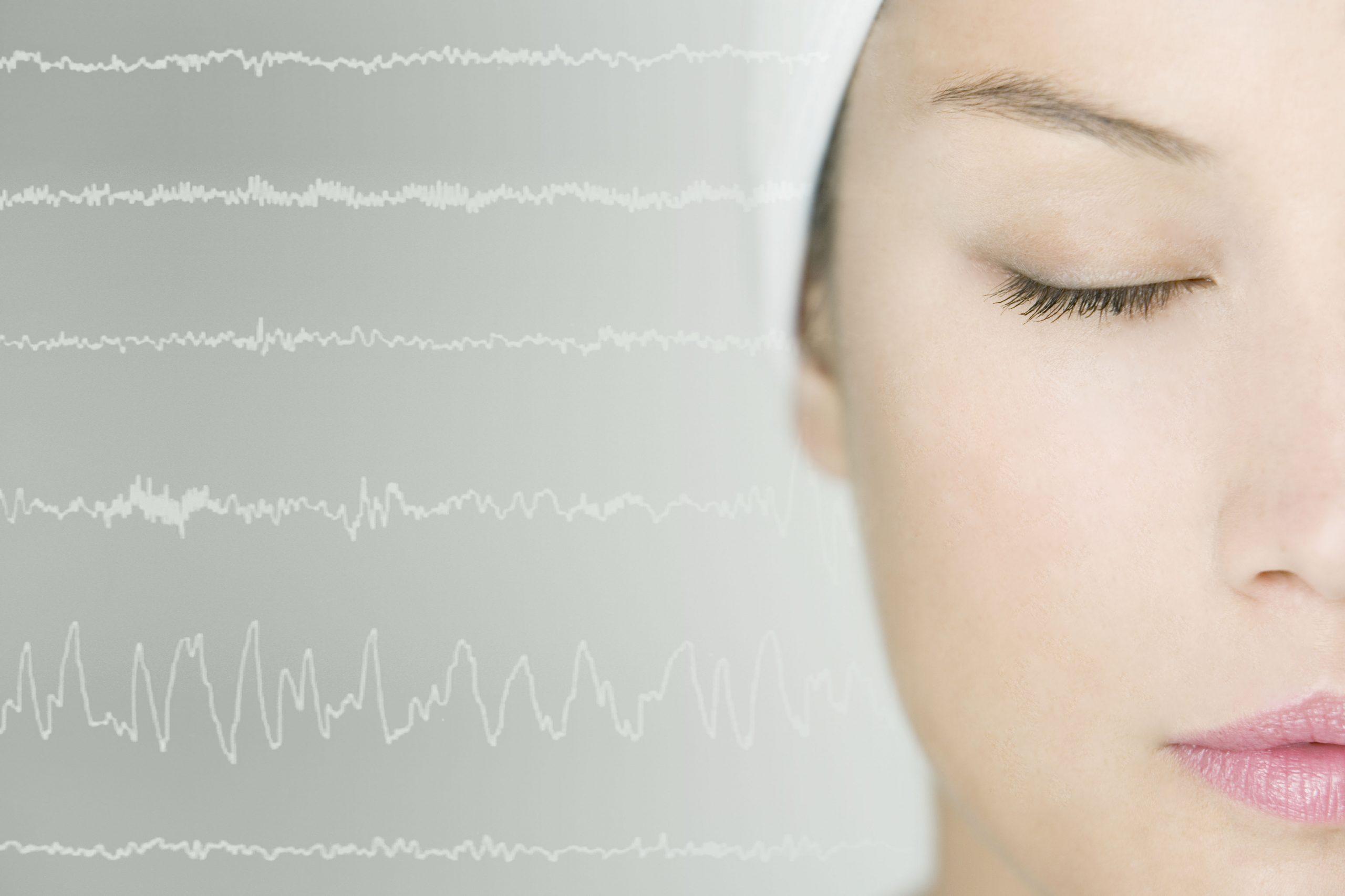 mujer con los ojos cerrados con ondas cerebrales