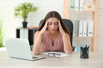 Woman,Suffering,From,Headache,In,Office